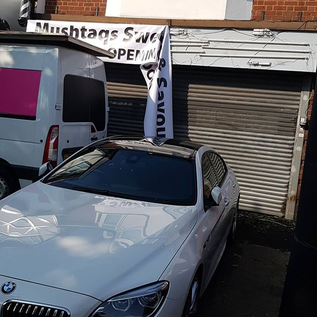 Putting up this 18 foot wide PVC banner. I Only whish the BMW wasn't in the way. Nice car though To place your order whatsapp me: Mak of Big Print Birmingham on 07702153393